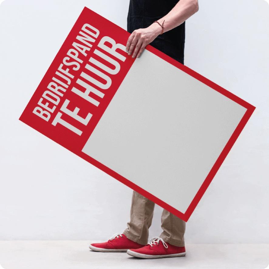 Man houdt 'Bedrijfspand Te Huur' poster vast