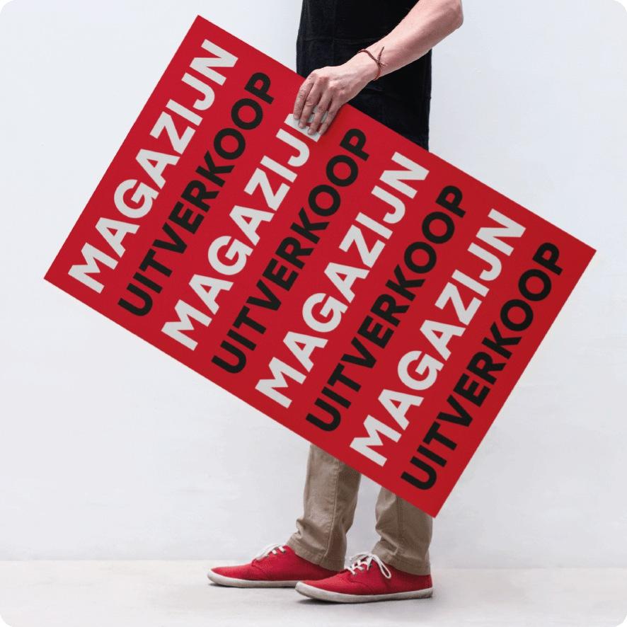 Man houdt 'Magazijn Uitverkoop' poster vast
